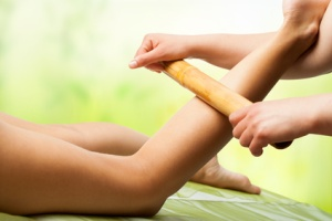Bamboo massage on female leg.